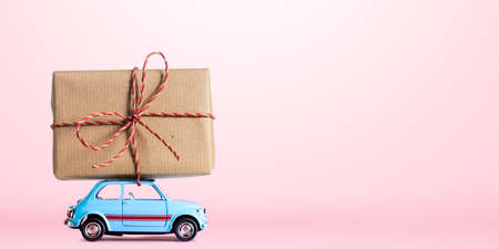 Blue retro toy car delivering gift box for Valentines day on pink background