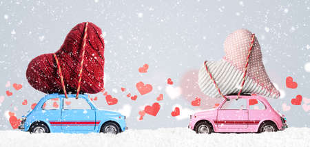 Couple of retro toy cars delivering craft hearts for Valentines day on gray background with flying hearts