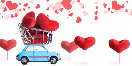 Blue retro toy car delivering craft heart for Valentines day on white background with flying hearts