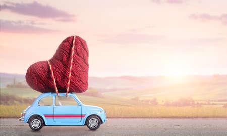 Blauwe retro speelgoed auto leveren hart voor Valentijnsdag tegen wazig zons ondergang plattelands landschap