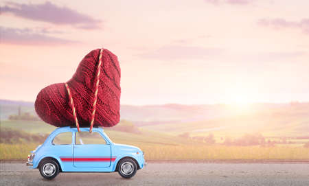 Blue retro toy car delivering heart for Valentines day against blurred sunset rural landscape