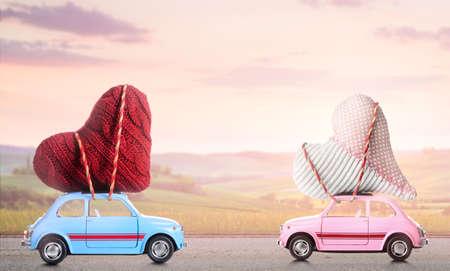 Paar van retro speelgoed auto's leveren ambachtelijke harten voor Valentijnsdag tegen wazig zons ondergang plattelands landschap