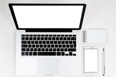 computer screens: Modern laptop computer and smartphone with blank screens on white table, view from above Stock Photo