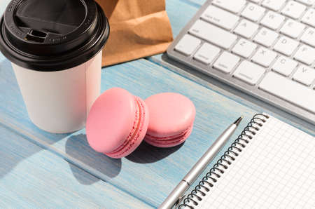 Working on the go. White modern keyboard with coffee cup, candies and notepad on blue wooden table at sunny weather Stock Photo