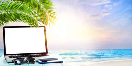 Modern laptop on blue wooden table with blank screen at tropical beach Stockfoto