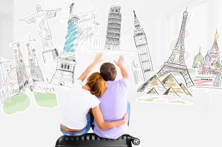 Couple planning their trip around the world and picking places to visit sitting on travel case photo