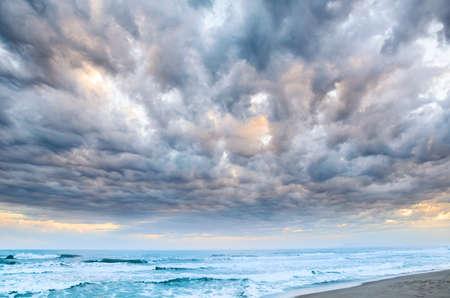 海辺で劇的な曇り日没