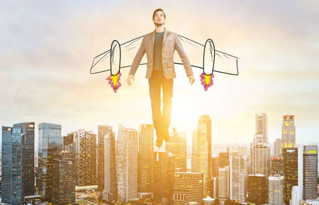 Business Advantage. Businessman with sketch wings hovering over down town on sunset. Imagens