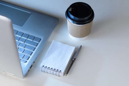 keyboard: Modern laptop on evening work place, coffee cup and notebook with pen, view from above