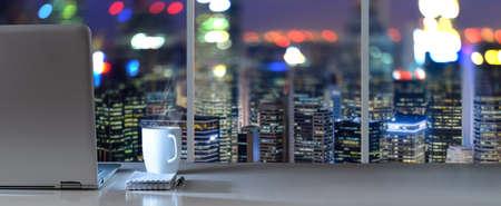 ビジネス地区に近代的なダウンタウンの摩天楼のパノラマ夜景とオフィスでテーブルのノート パソコン