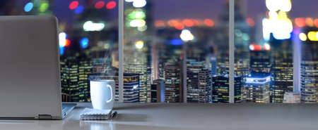 Laptop on table in office with panoramic night view of modern downtown skyscrapers at business district Stockfoto