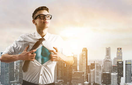 tearing down: Business superhero. Young businessman showing super hero suit under his shirt down town on sunset. Stock Photo