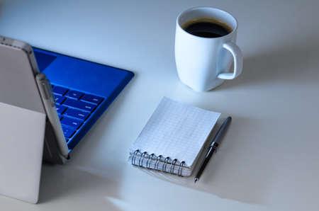 現代のラップトップ夕方職場、コーヒー カップ、ペンとノート、上からの眺め
