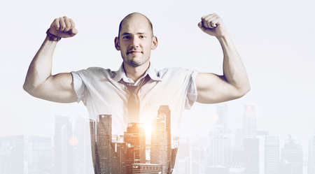Strong businessman double exposure concept. Business man showing muscular hands, mixed with sunset city skyline