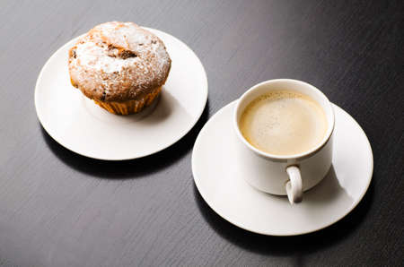 cup of coffee and muffin on black table, view frim above