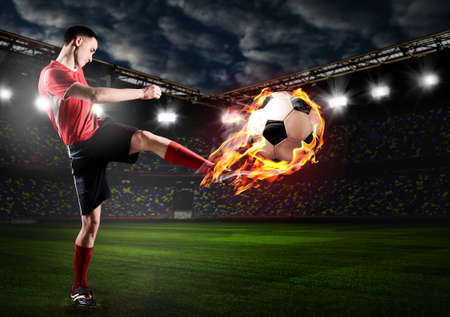 soccer or football player is kicking ball on stadium photo