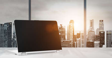 파노라마 일몰과 함께 사무실에서 테이블에 노트북 비즈니스 지구, 빈 화면에서 현대 시내 고층 빌딩의보기