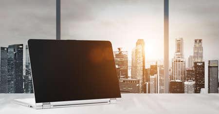 Laptop op tafel in kantoor met panoramisch uitzicht op de zonsondergang van moderne wolkenkrabbers in het centrum van de binnenstad, leeg scherm