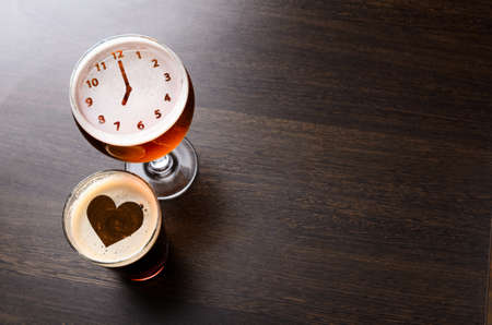 Heart and clock silhouettes in two glasses of fresh beer on pub table, view from above