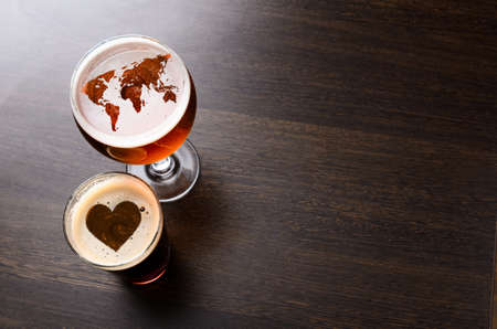 draughts: World map and heart silhouettes on foam in beer glass on pub table, view from above. Elements of this image furnished by NASA