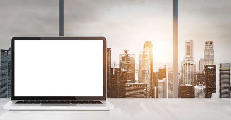 Laptop on table in office with panoramic sunset view of modern downtown skyscrapers at business district, blank screen