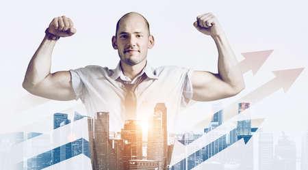 Fuerte concepto de doble exposición de empresario. Hombre de negocios que muestra manos musculares, mezclado con horizonte de la ciudad al atardecer Foto de archivo - 80265900