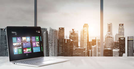 Laptop on table in office with panoramic sunset view of modern downtown skyscrapers at business district photo