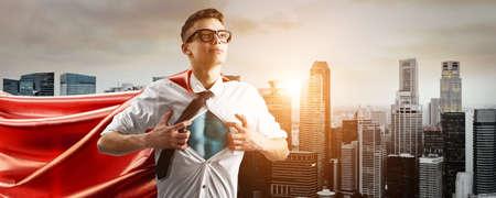 비즈니스 영웅입니다. 일몰에 마을 내려 그의 셔츠 아래 슈퍼 영웅 소송을 보여주는 젊은 사업가.