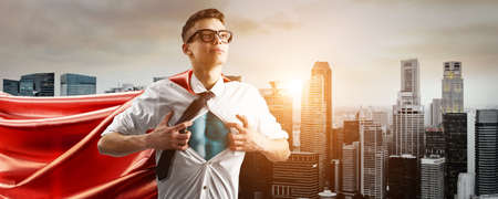 Business superhero. Young businessman showing super hero suit under his shirt down town on sunset. Stock Photo