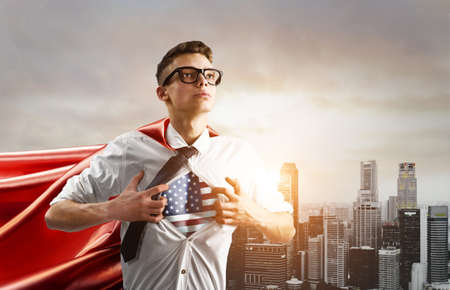 USA Superhero. Young businessman showing American flag under his shirt against sunset city.