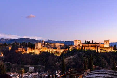 Alhambra fortress night view against Sierra Nevada mountains, Granada, Spain