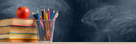 Terug naar school. Accessoires, boeken en verse appel tegen schoolbord