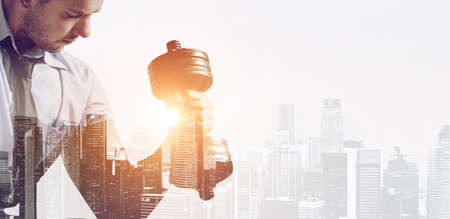 Hard working business concept. Strong businessman with dumbbell mixed with sunset city skyline Reklamní fotografie