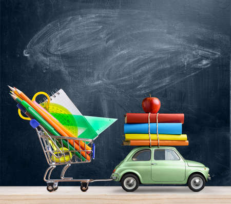 Back to school sale background. Car delivering shopping cart with accessories, books and apple against blackboard. Archivio Fotografico