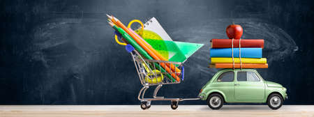 Back to school sale background. Car delivering shopping cart with accessories, books and apple against blackboard. 스톡 콘텐츠