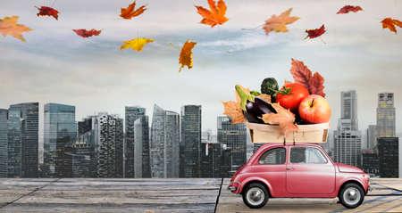 Entrega de comida. Coche de juguete rojo otoño con hojas caídas entrega de frutas y verduras contra edificios del distrito de negocios