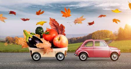Coche de juguete rojo otoño con hojas caídas entrega de frutas y verduras contra el paisaje rural puesta del sol