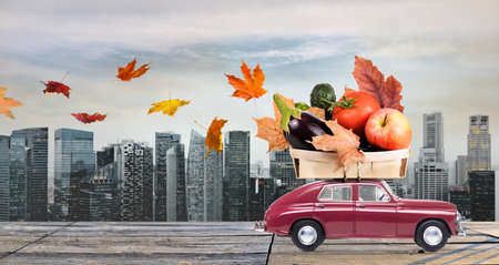 Food delivery. Autumn red toy car with fallen leaves delivering fruits and vegetables against business district buildings