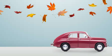 Autumn red toy car with fallen leaves against minimalistic blue background