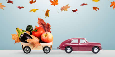 Food delivery. Autumn red toy car with fallen leaves delivering fruits and vegetables against minimalistic blue background