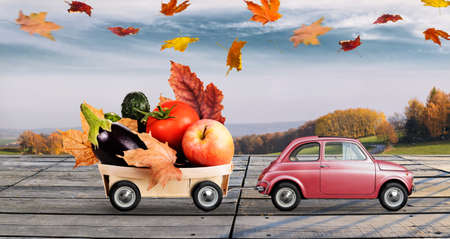 Autumn red toy car with fallen leaves delivering fruits and vegetables against sunset rural landscape