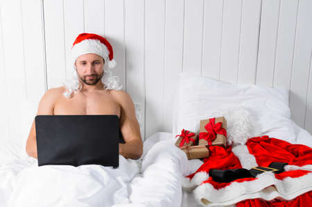 Santa Claus in hotel room without costume shopping for Christmas or New Year