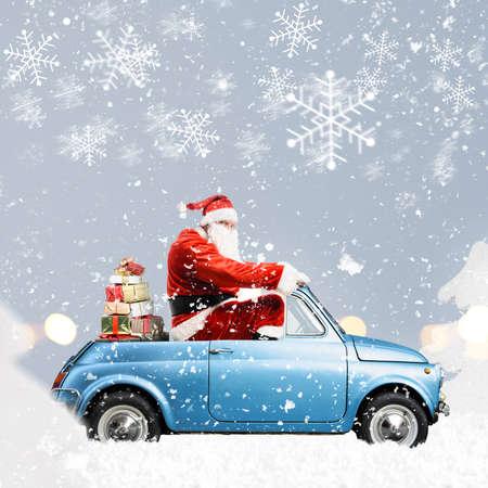 Babbo Natale in automobile che trasporta i regali di Natale o di Capodanno a sfondo grigio nevoso Archivio Fotografico - 88529886