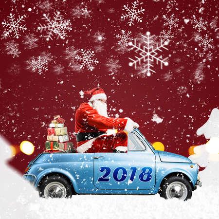 Babbo Natale in auto consegna regali di Natale o Capodanno a sfondo rosso innevato Archivio Fotografico - 88529909
