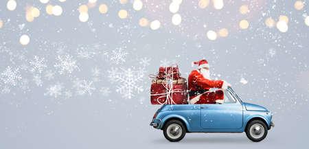 눈 덮인 회색 배경에서 크리스마스 또는 새해 선물을 제공하는 차에 산타 클로스