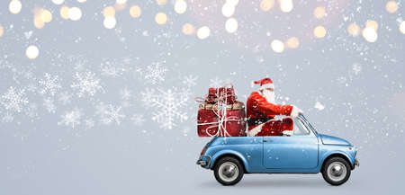 Santa Claus on car delivering Christmas or New Year gifts at snowy gray background