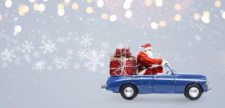 雪に覆われた灰色の背景でクリスマスまたは新年の贈り物を提供する車のサンタ クロース 写真素材