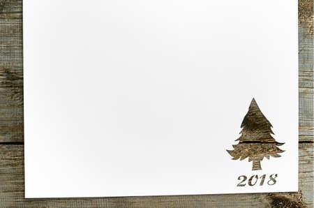 Tagliare la carta in forma di abete per carta natale 2018 o Capodanno sul tavolo di legno Archivio Fotografico - 90799580