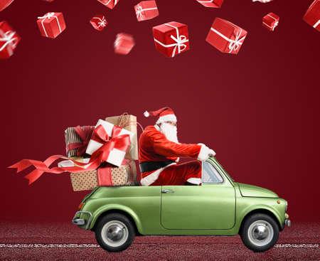Santa Claus auf dem Auto, das Weihnachten oder Neujahrsgeschenke am roten Hintergrund liefert Standard-Bild - 91450381