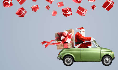 Santa Claus on car delivering Christmas or New Year gifts at gray background Stock Photo